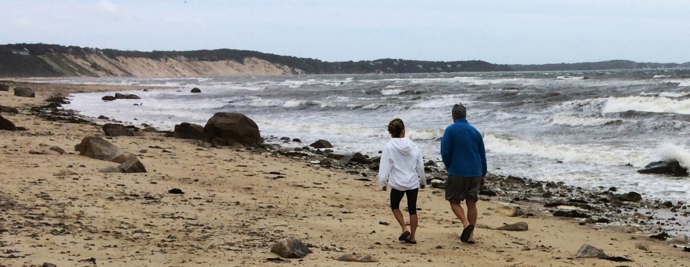 A couple walk along Sagamore Beach in Bourne, Mass., on Monday as Hermine whips up heavy surf on Cape Cod Bay and churns hundreds of miles out in the Atlantic Ocean.