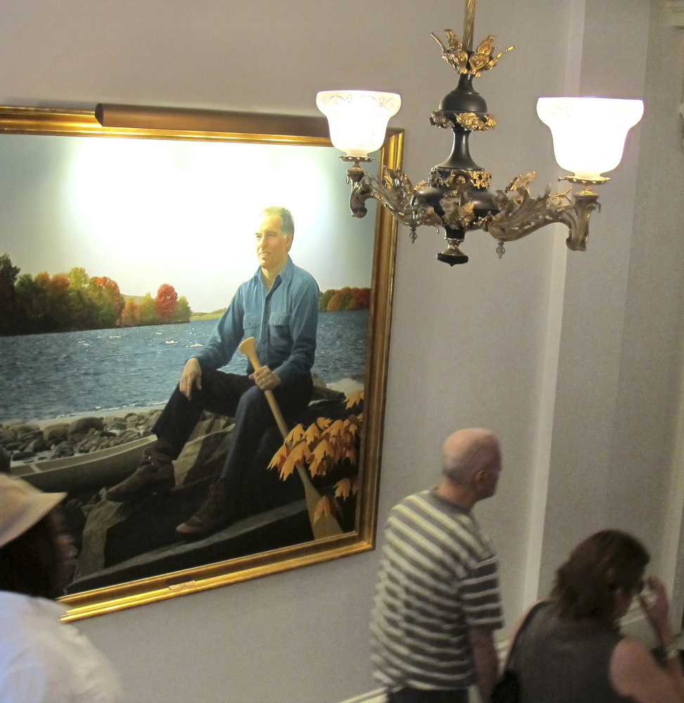 People walk past the official portrait of former Vermont Gov. Howard Dean. Vermont Statehouse curator David Schutz says the state has images of all but five of its 81 governors.