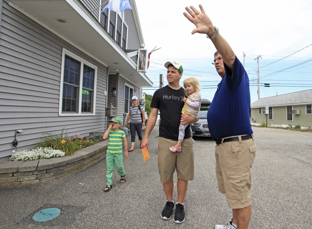"Mike Bouffard, owner of the Normandie Inn in Old Orchard Beach, points out a room location while helping the Adam family from Quebec check in Monday morning. The family had been motel-hopping since Wednesday as prices and availability fluctuated over the holiday weekend. Labor Day weekend capped an extra busy season for Bouffard. He said, ""The Canadians took it on the chin with the exchange rate,"" but good weather kept motels full."
