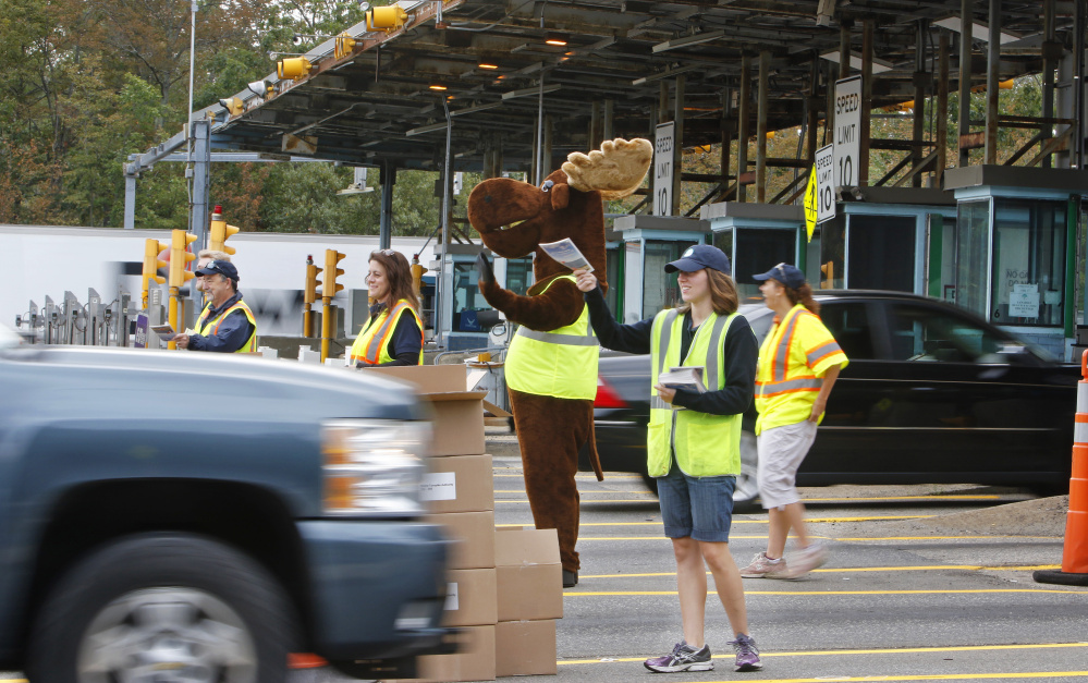 Drivers going south on the Maine Turnpike on Monday morning are greeted at the York toll plaza by Miles the Moose and Claudette the Lobster, along with turnpike authority employees who handed out copies of the 2017 Farmers' Almanac. Jill Brady/Staff Photographer
