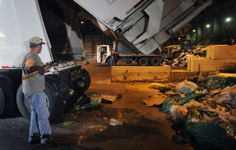 Randy Spaulding of Agri-Cycle Energy uses a rake to remove food waste from the back of a truck after it unloaded at ecomaine in Portland. The plant may handle 5,000 tons of food waste in the first year.
