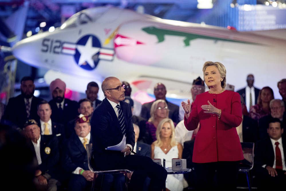 """Hillary Clinton, with """"Today"""" show co-anchor Matt Lauer, speaks at the forum on national security Wednesday night at the Intrepid Sea, Air and Space museum in New York. She urged voters to weigh her readiness to be president based on """"the totality of my record."""""""