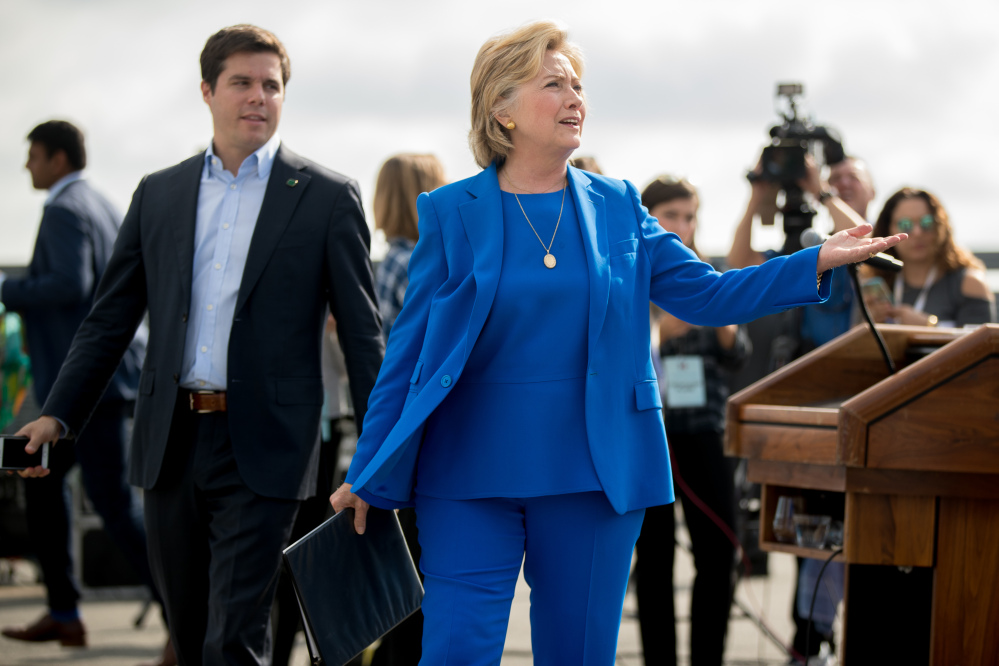 Democratic presidential nominee Hillary Clinton, accompanied by traveling press secretary Nick Merrill, left, reacts to a reporter's question as she finishes speaking to members of the media before boarding her campaign plane at Westchester County Airport in White Plains, N.Y., on Thursday.