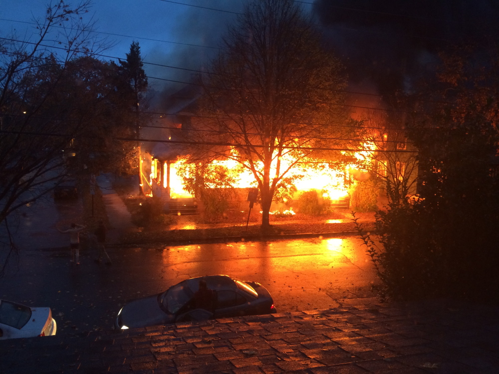Flames engulf the building at 20-24 Noyes St. shortly after 7 a.m. on Nov. 1, 2014. The cause of the fire was found to be a discarded cigarette that ignited materials on the front porch.