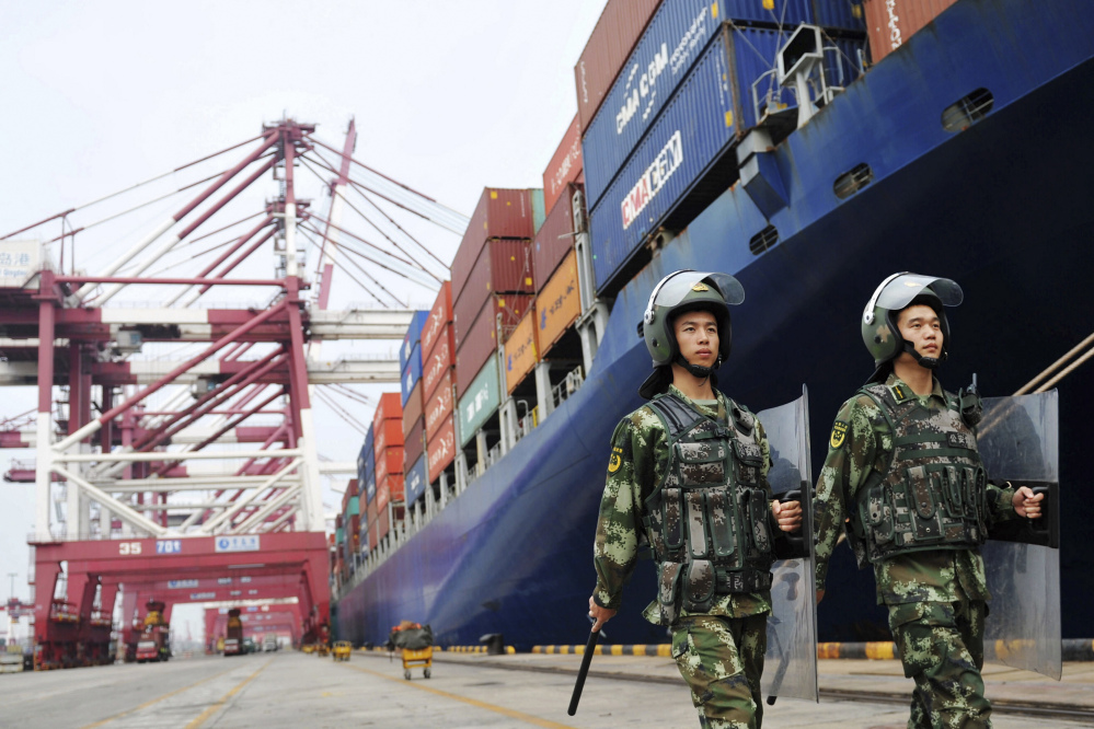 China's paramilitary police patrol as containers are loaded on to a cargo ship for export at a port in Qingdao in east China's Shandong province Thursday. China's exports rose in August for the first time in two years.