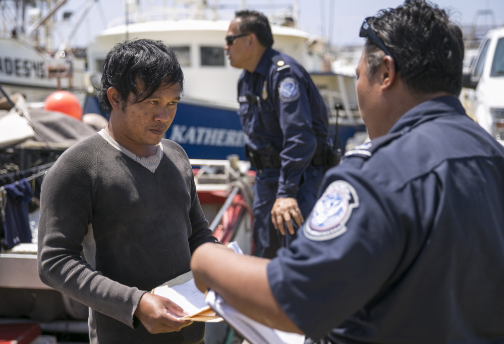 In Hawaii, U.S. Customs and Border Protection officer Ericson Padilla checks the documents of an Indonesian fisherman who might spend weeks in cramped, dangerous quarters at sea while earning wages that won't go far outside the Third World. Marco Garcia/Associated Press