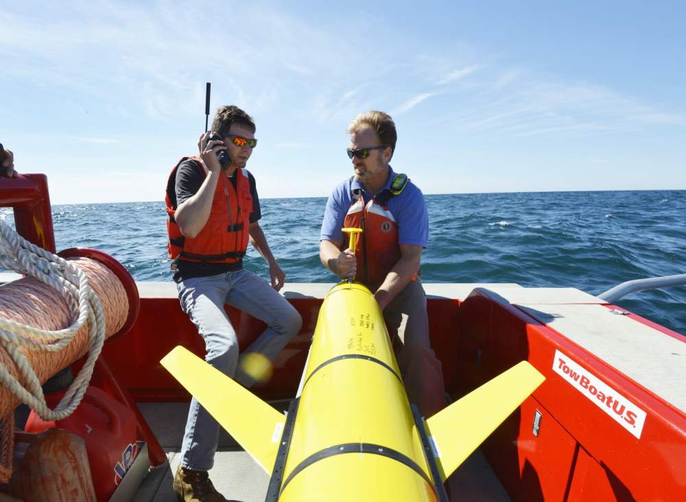 Woods Hole Oceanographic Institution engineers prepare to release a drone off Martha's Vineyard on Sept. 2. The 'ocean gliders' allow researchers to collect data on water temperatures, salinity and density before and after storms.