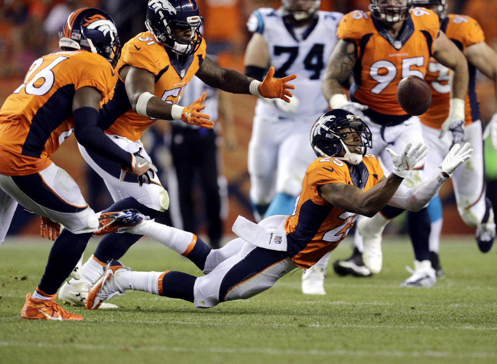Denver Broncos cornerback Chris Harris intercepts the ball against the Carolina Panthers to set up a touchdown run during the second half Thursday in Denver.