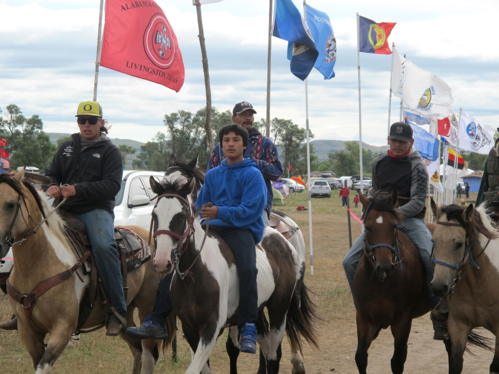 "Horseback riders make their way through an encampment near North Dakota's Standing Rock Sioux reservation on Friday. The Standing Rock Sioux tribe's attempt to halt construction of an oil pipeline near its North Dakota reservation failed in federal court Friday, but three government agencies asked the pipeline company to ""voluntarily pause"" work on a segment that tribal officials say holds sacred artifacts."