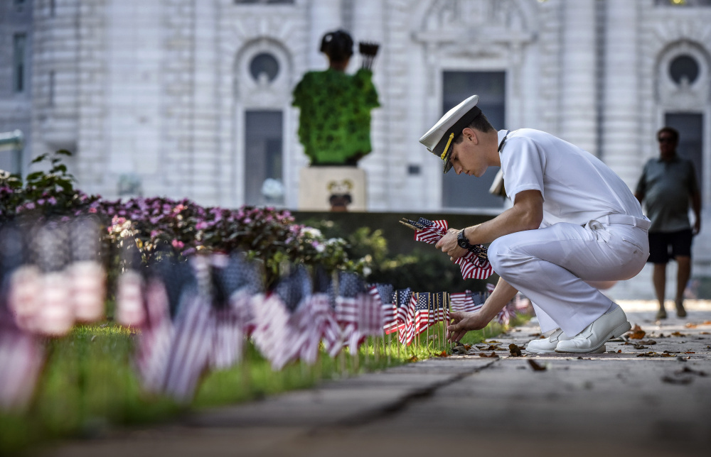 Midshipman Shawn Picciott places one of 2,996 flags on Stribling Walk, representing those lost on 9/11, at the U.S. Naval Academy in Annapolis, Md.