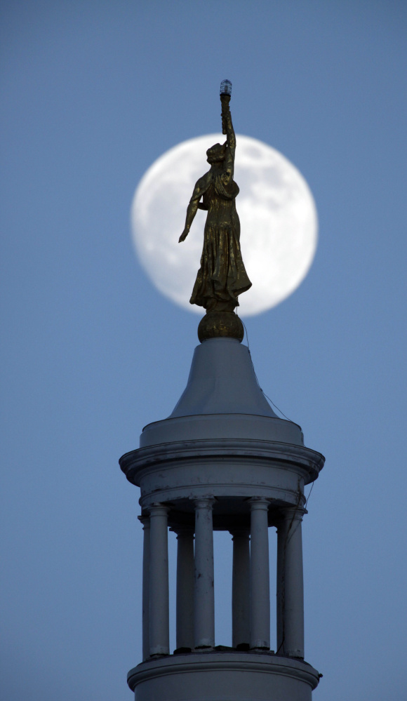 Associated Press/Robert F. Bukaty Somethging from story , pls The nearly-full moon rises behind the draped female figure of Wisdom on top of the Maine state house, Friday, Jan. 9, 2009, in Augusta, Maine. Earlier in the day at the state house Gov. John Baldacci unveiled  his two-year state budget that proposes deep cuts in spending that include the elimination 219 state positions and a 2.4 percent cut in college funding. (AP Photo
