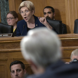 "Senate Banking Committee member Elizabeth Warren, D-Mass., blasts Wells Fargo CEO John Stumpf, foreground, during the committee's hearing Tuesday. ""You squeezed your employees to the breaking point so they would cheat customers,"" she said. ""You should resign."""