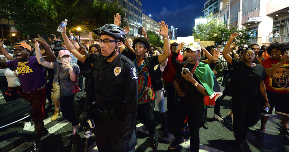 Protestors march behind a bicycle officer along Trade Street in Charlotte, N.C., on Wednesday night. The protestors were marching and rallying against a police officer's fatal shooting of Keith Lamont Scott on Tuesday evening. Authorities tried to quell public anger, but a prayer vigil turned into a second night of violence.