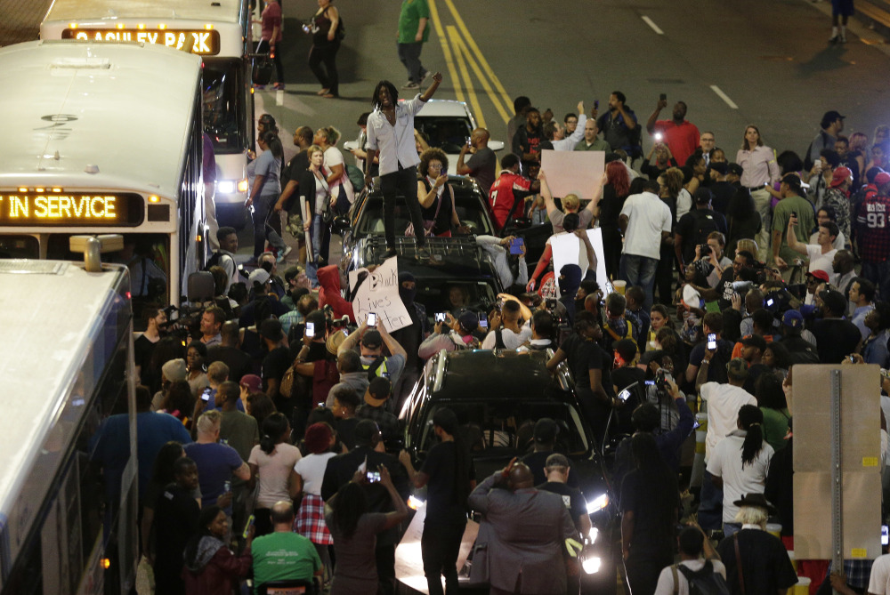 Demonstrators in Charlotte, N.C., protest Wednesday night against the fatal police shooting of Keith Lamont Scott. Protesters rushed police in riot gear at a downtown Charlotte hotel and officers fired tear gas to disperse the crowd.
