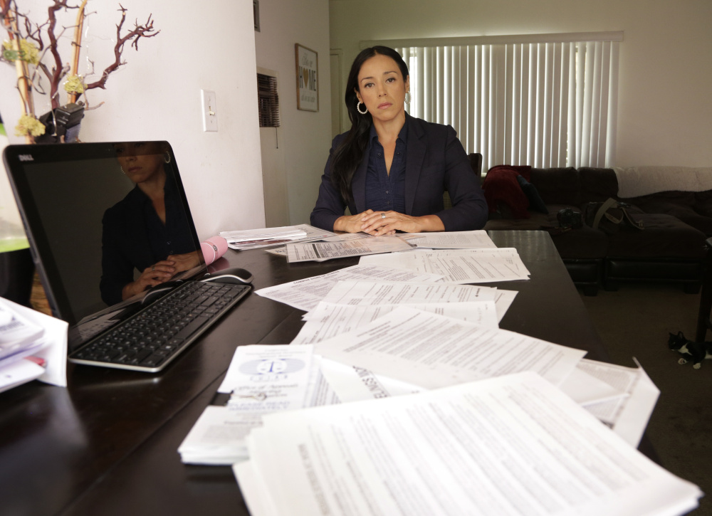 Ruth Landaverde, a former worker at Wells Fargo and Bank of America, displays documents supporting her allegations of unrealistic sales goals at her home in Glendale, Calif. She's one of many former employees who say retail banks have become high-pressure sales centers.
