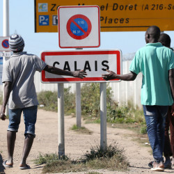 "Migrants pass by a road near the camp called ""the Jungle"" in Calais, France. Camp conditions are ""not acceptable"" and ""extremely difficult"" French President Francois Hollande said."
