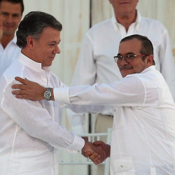 Colombia President Juan Manuel Santos, left, and the top commander of a longtime rebel army, Rodrigo Londono, shake hands after signing a peace accord Monday.