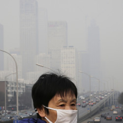 A woman wears a mask to protect against pollution last year in Beijing. The World Health Organization says one in nine deaths globally links to pollution.