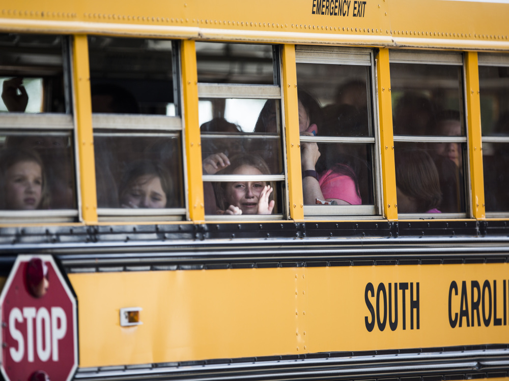 A Townville Elementary student looks out the window of a school bus as she and her classmates are transported to Oakdale Baptist Church, following a shooting at the school in Townville on Wednesday.