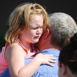 Lilly Chapman, 8, cries after being reunited with her father, John Chapman at Oakdale Baptist Church on Wednesday in Townville, S.C., after a teenager opened fire at the school.