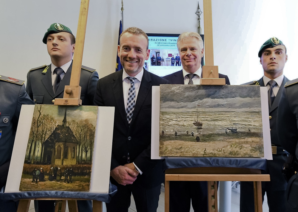 """Director of Amsterdam's Van Gogh Museum Axel Rueger, center, stands next to the paintings """"Congregation leaving the Reformed Church of Nuenen,"""" left, and the 1882 """"Seascape at Scheveningen"""" by Vincent Van Gogh, during a news conference in Naples, Italy, on Friday. The paintings were stolen from the museum in 2002."""
