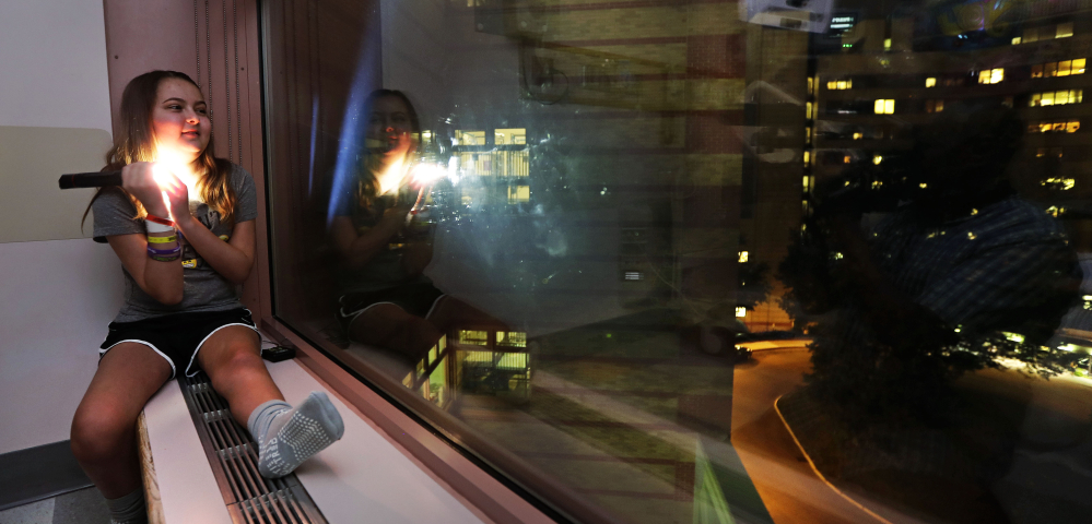 """Olivia Stephenson of Lincoln, R.I., covers the lens of a flashlight as she messages back two light pulses, meaning """"thank you,"""" to people in surrounding buildings from her hospital room in Providence, R.I. Businesses around the Hasbro Children's Hospital flash their lights on and off every night as a way to say goodnight to sick children inside. At right, skyline lights illuminate downtown as seen from the hospital."""
