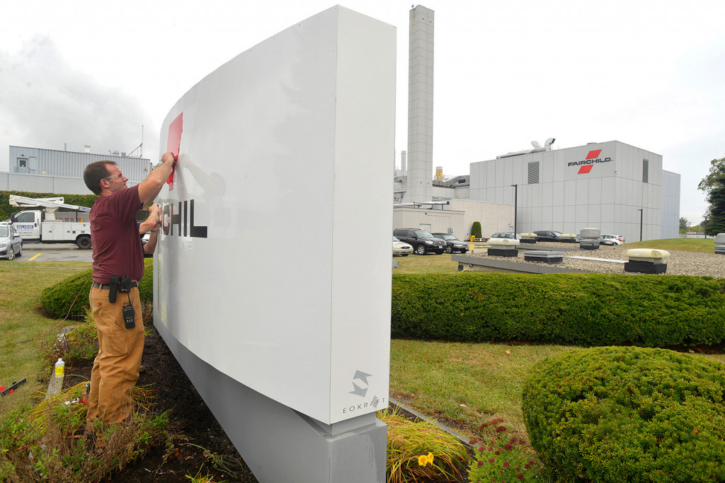Workers took down the signs for Fairchild Semiconductor in South Portland on Monday after its acquisition by ON Semiconductor.