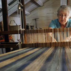 Paula Taggart of Parsonsfield, a volunteer with the 19th Century Willowbrook Village in Newfield, weaves with a barn loom in July 2011. File photo/Shawn Patrick Ouellette: