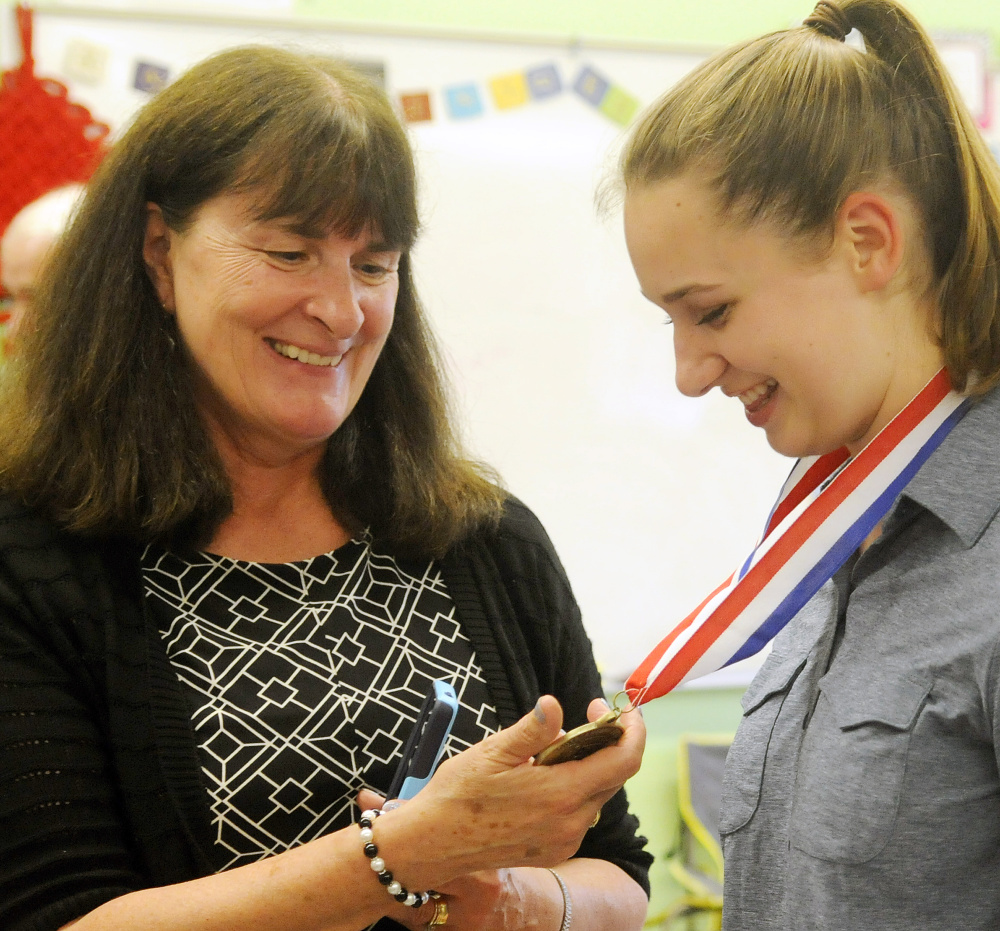 Monmouth Academy English teacher Christine Arsenault examines a medal presented to student Maddie Amero on Thursday for making a film with classmates that won best presentation from Maine at the National History Day Competition in Washington, D.C.