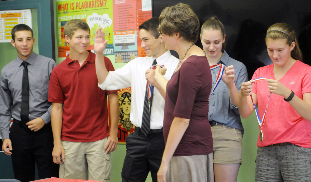 Monmouth Academy students Devon Poisson, left, Dylan Goff, Cody Roy, Maddie Amero, second from right, and Abbey Allen, right, receive medals Thursday from teacher Jocelyn Gray, center, at the school. The juniors won best presentation from Maine at the National History Day Competition in Washington, D.C. for a documentary about the Acadian deportation from Canada in the 1700s.