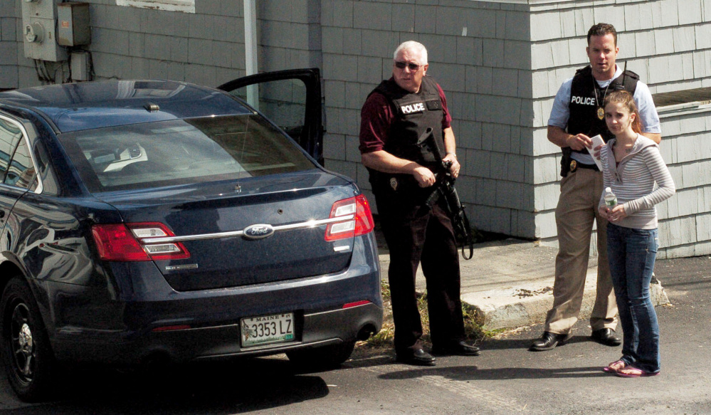 Waterville Police Chief Joe Massey, left, and officer Damon Lefferts interview a woman who is reportedly a friend of a man who was assaulted and injured at 11 Union St. on Thursday. Zachary Larrabee, 31, who lives on College Avenue, was arrested and charged with assault and criminal threatening later Thursday.
