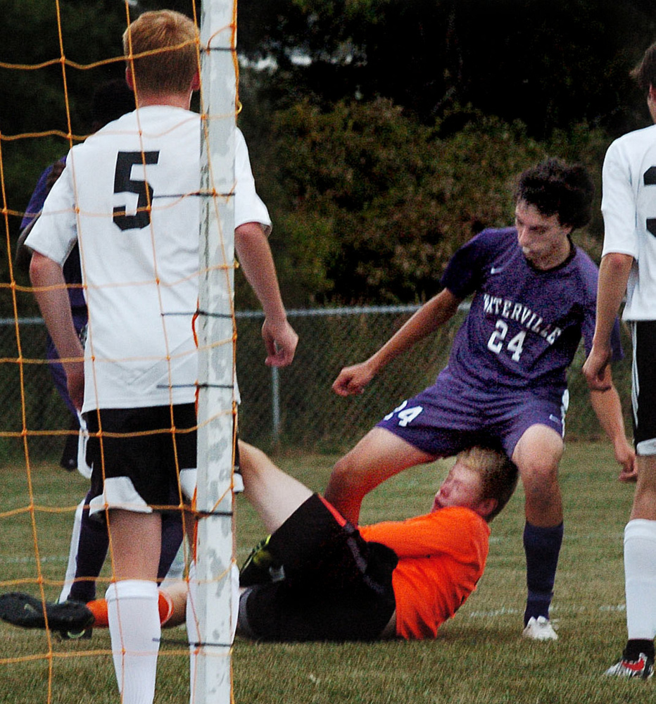 Winslow goalie Jake LaPierre covers the ball under pressure from Waterville's Ethan Nurick on Tuesday in Winslow. Winslow's Brice Hiller is at left.