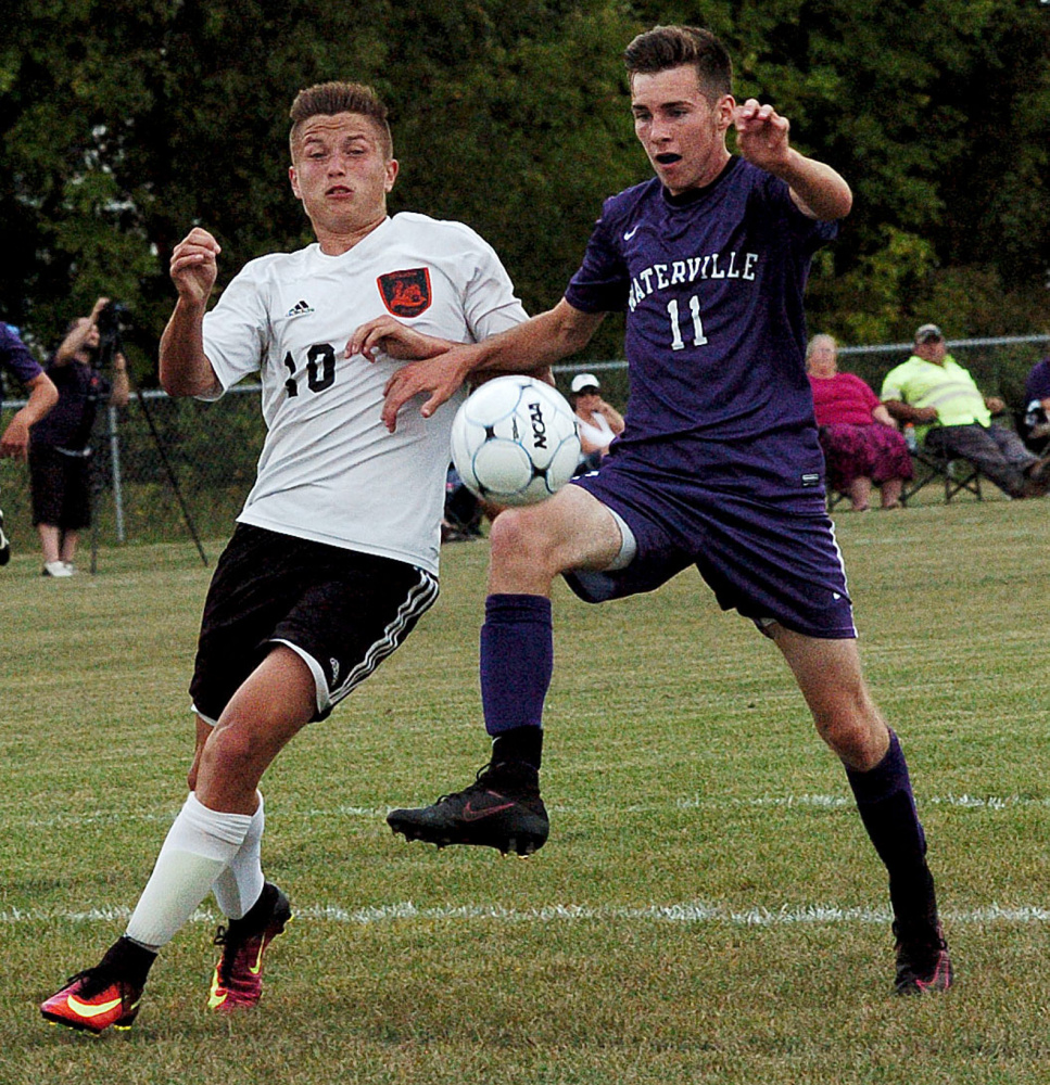 Winslow's Michael Wildes, left, and Waterville's Ethan Cayer go after the ball during a game Tuesday in Winslow.