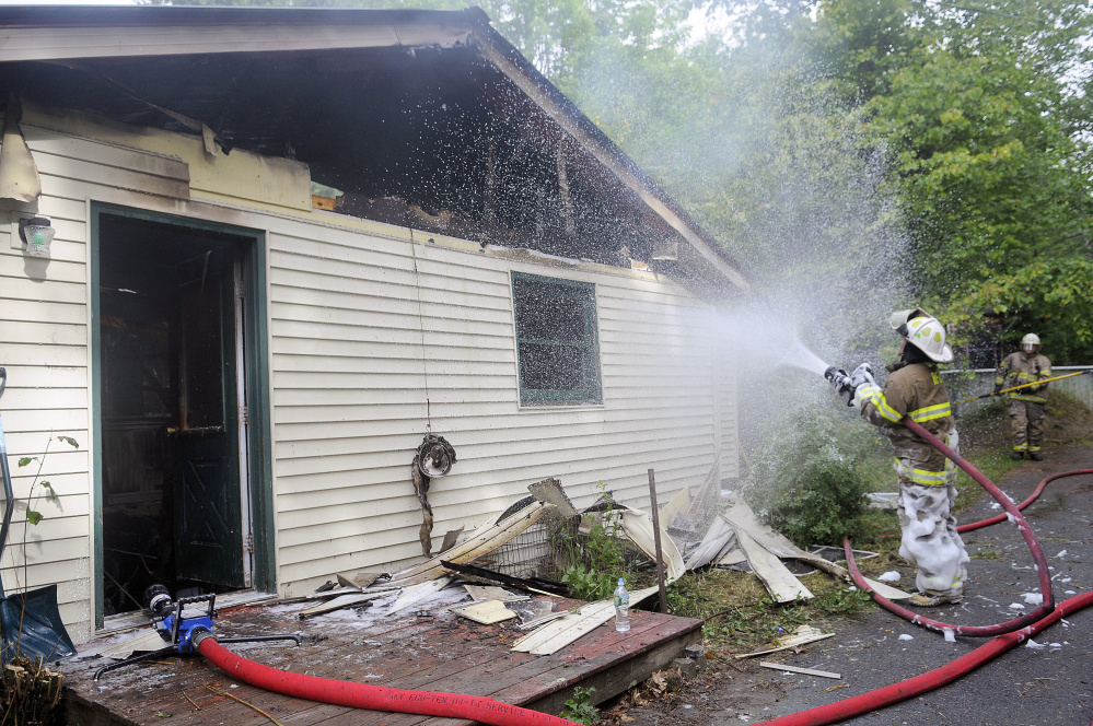 Firefighters extinguish a blaze Wednesday that heavily damaged a Mount Vernon home on Barbioni Lane, a private road near 402 Belgrade Road.