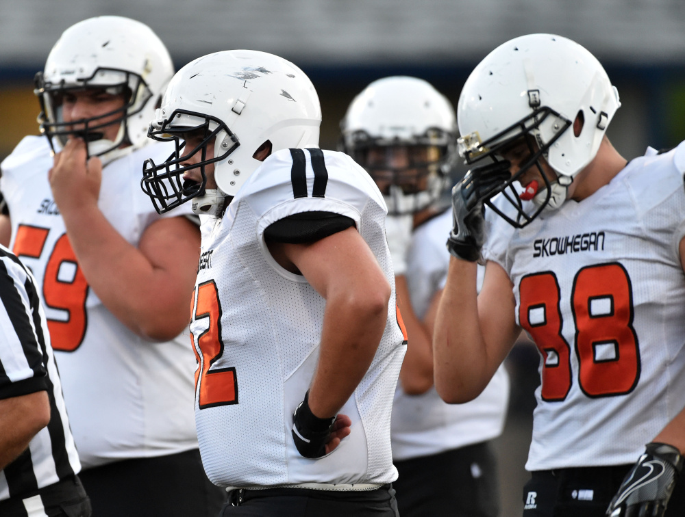 Skowhegan two-way tackle Owen Boardman, middle, takes a breather during a game against Lawrence last Friday.