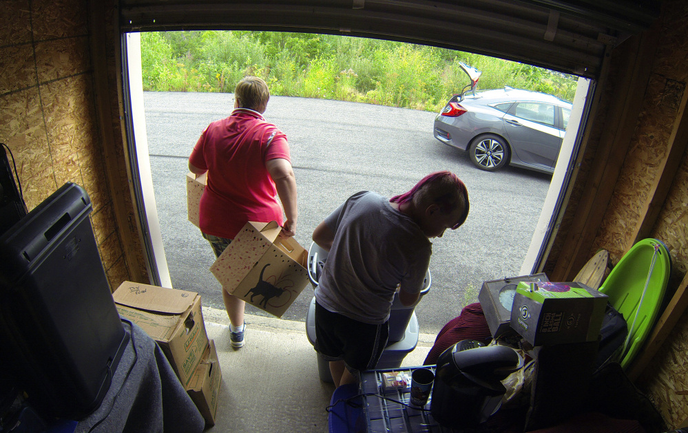 Navy veteran Alicia Barnes, left, and son Joe Bowman move things to her car on Sept. 2 at ABC Self Storage in Chelsea. They were taking things out of storage to move them into an apartment she recently leased.