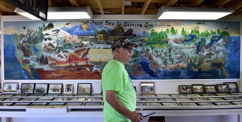 Buddy Frost, president of the Clinton Historical Society, sits Friday in front of a mural painted by Viva Chamberlain in 1976 that's on display at the Clinton Lions Agricultural Fair in Clinton.