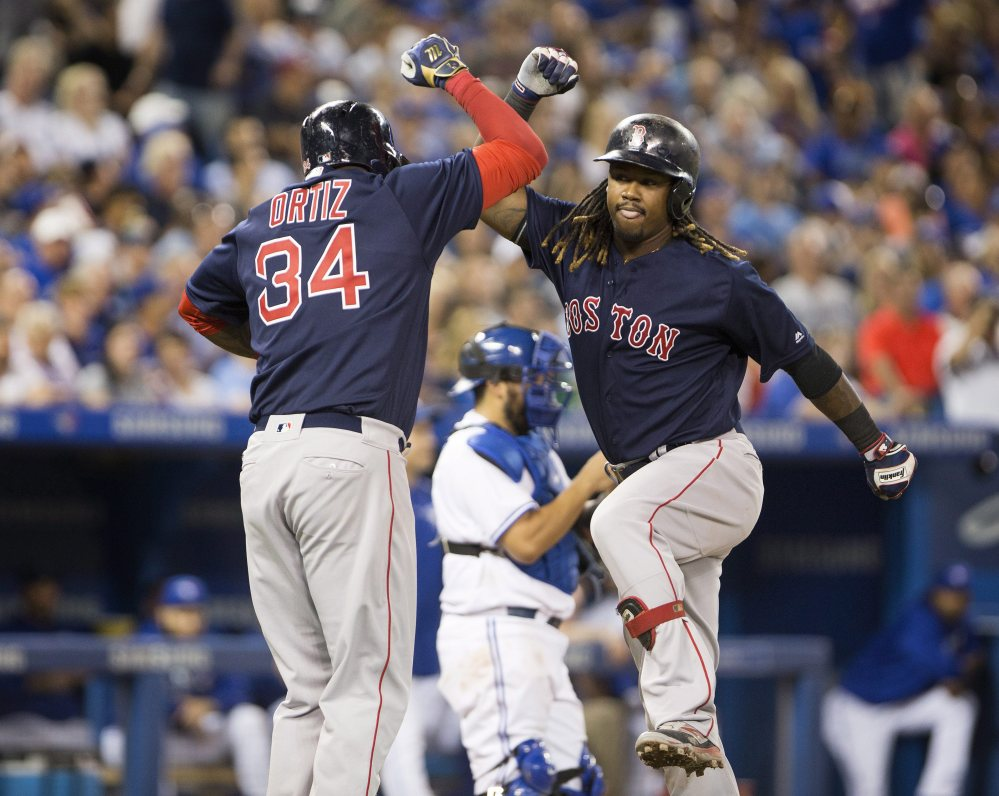 Bostonfirst baseman Hanley Ramirez, right, celebrates his seventh-inning three-run home run with David Ortiz against the Blue Jays in Toronto on Friday night.