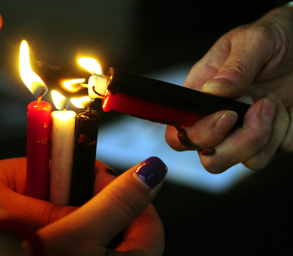 Vigil attendees light candles Saturday during The Addict's Mom Light of Hope event in Mill Park in Augusta.