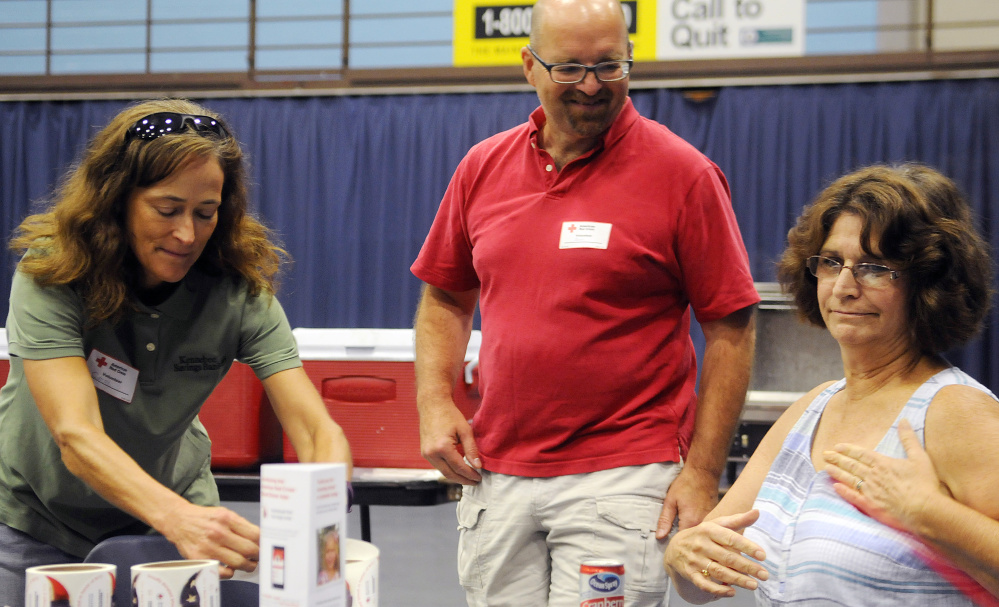 Red Cross volunteers Carol Payne, left, and Don Macomber assist blood donor Sue Baker during a drive Sunday in Augusta.