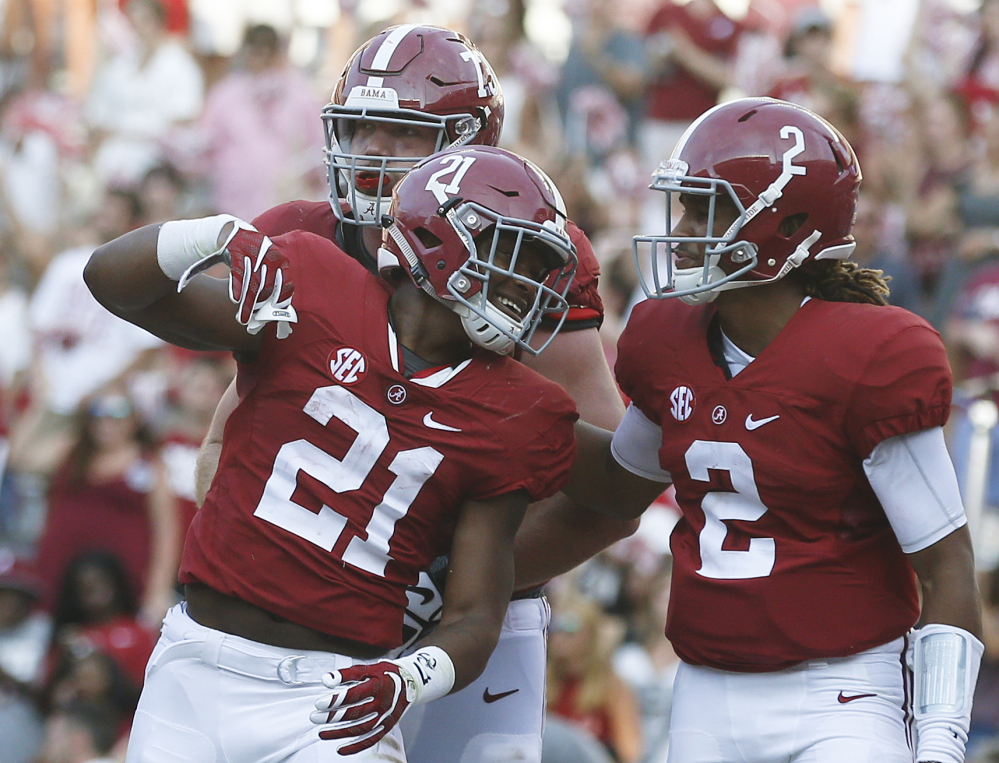 Alabama running back B.J. Emmons, center, quarterback Jalen Hurts, right, and offensive lineman Jonah Williams, back, celebrate after Emmons scored against Western Kentucky on Saturday in Tuscaloosa, Alabama.
