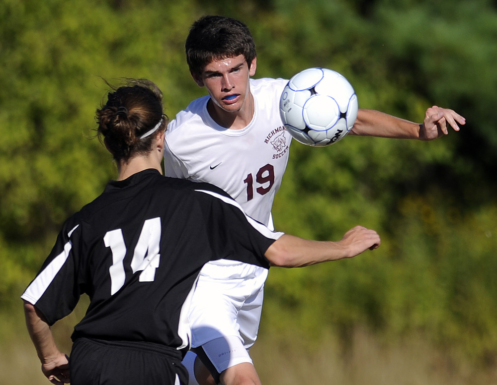 Richmond's Justin Vachon (19) knocks the ball past St. Dominic's Kyle Welsh during a game Monday in Richmond.