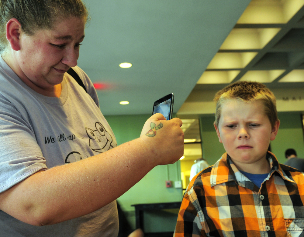 Blaze Moody, 7, of Guilford, right, makes a disapproving face after tasting a roasted cricket while his mother, Amber Moody, records it on her phone at the Entosense Inc. booth during Bug Maine-ia on Tuesday at the Maine State Museum in Augusta.