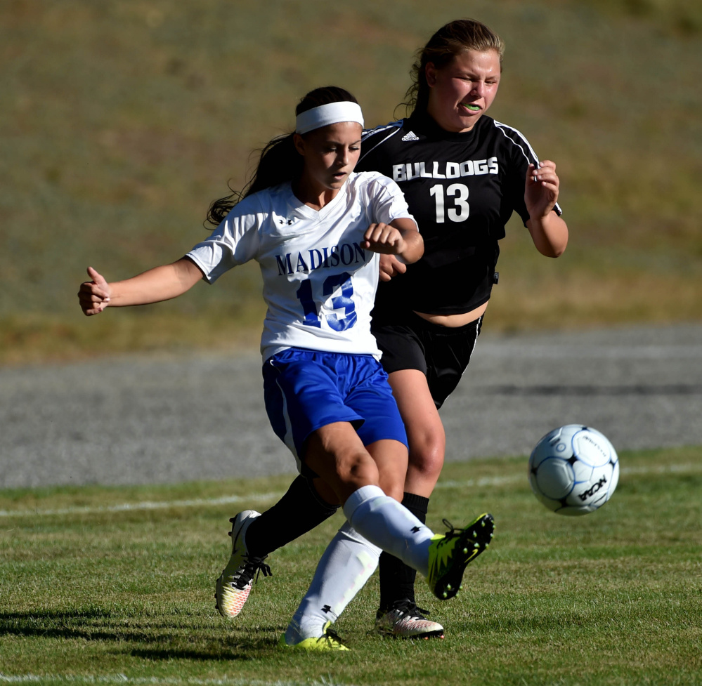 Madison freshman Emily Edgerly (13) looks to pass as Hall-Dale sophomore Grace Begin defends during a Mountain Valley Conference game Tuesday afternoon. Madison won, 6-0.