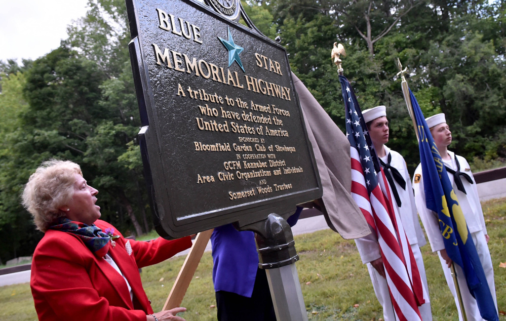 Debra Burnham, Blue Star marker chair, left, unveils the Blue Star Highway sign at the U.S. Route 2 rest area in Skowhegan on Wednesday.