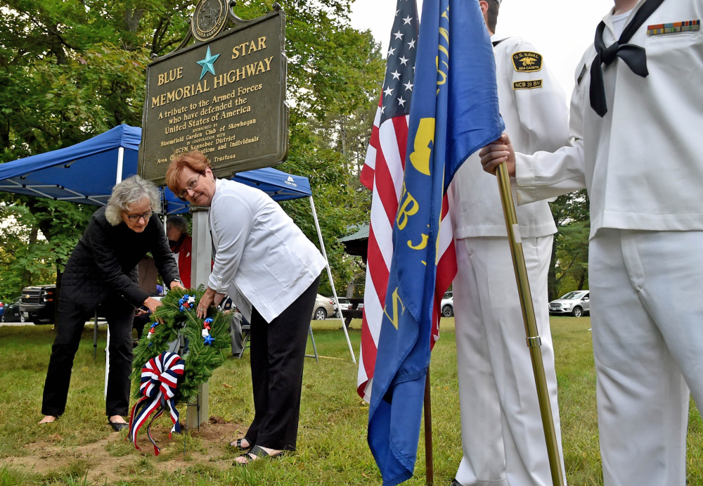 Members of the Blue Star marker committee, Jeanne Shay, left, and Davida Barter, center, present a wreath at the Blue Star Highway sign at the U.S. Route 2 rest area in Skowhegan on Wednesday.