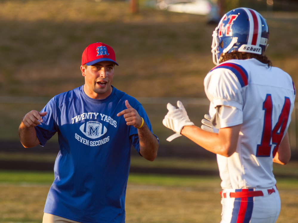 Messalonskee assistant football coach Kyle Bishop talks to Zak Bickford during warmups for a Pine Tree Conference Class B game against Cony last Friday at Alumni Field in Augusta.