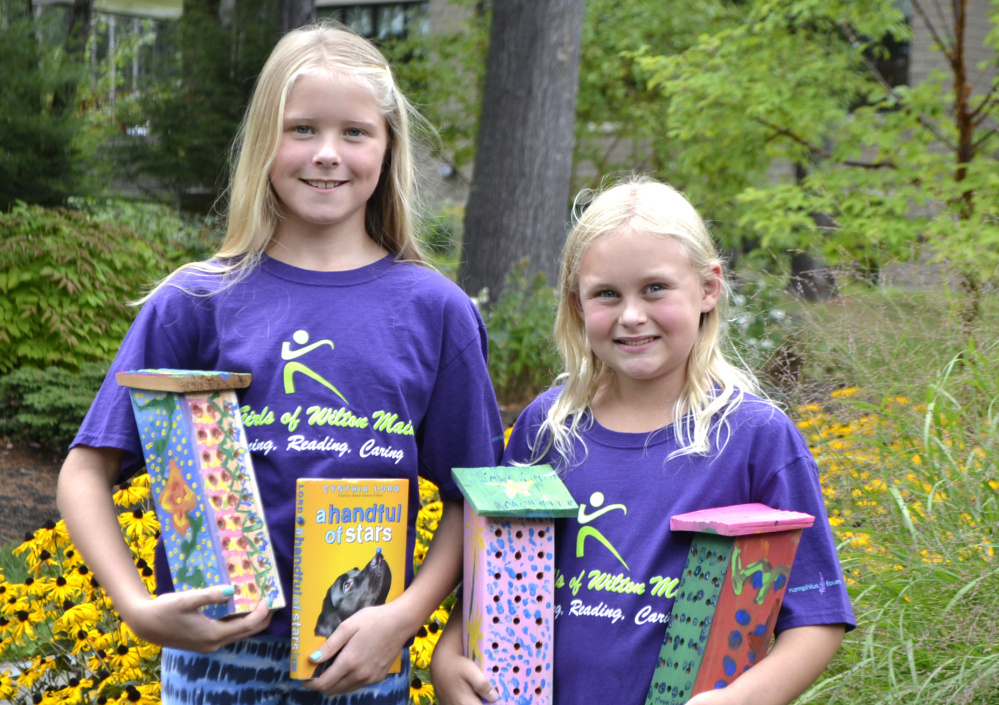 Contributed photo Two summer campers of the Fit Girls of Wilton, Lucinda Carroll, left, and Maddie Morton, pose with their painted bee houses at Franklin Memorial Hospital's healing garden.
