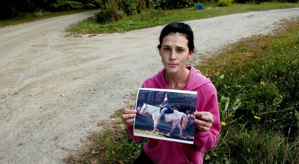 Sierra Miner holds a photograph of her and her 4-year-old mare, Lucy, on Thursday at the spot she said someone drove onto her property in Canaan a day earlier and struck and dragged the tethered horse to her death.