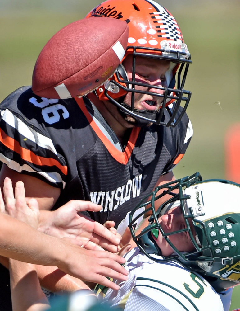 Staff photo by Michael G. Seamans   Mount Desert Island's Colby Lee (5) fumbles the ball as he is tackled by Winslow's Kenny Rickard (36) on Saturday in Winslow.